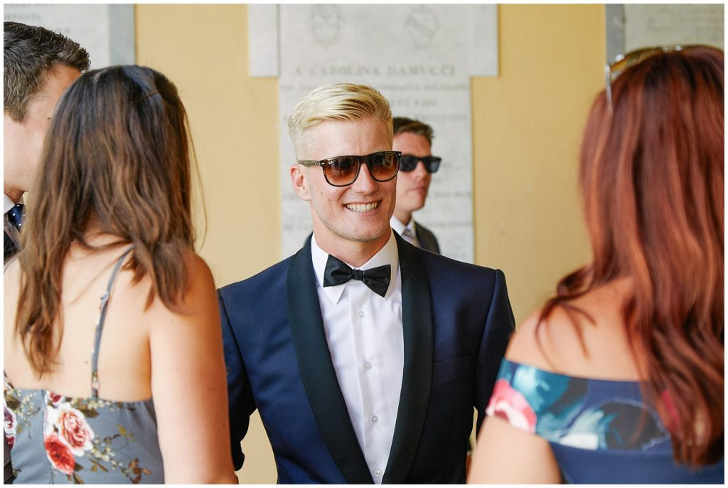 Groom smiling and greeting guests outside the Church at his Italian destination wedding