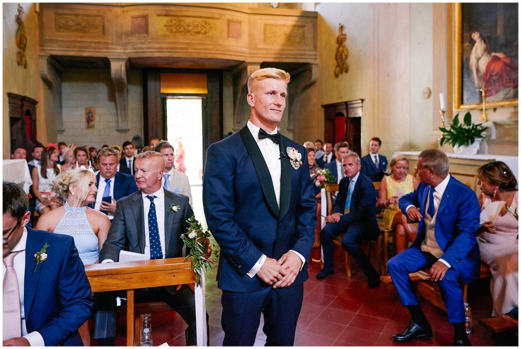 Groom stood at the alter with friends at family behind him at the Catholic Church of Careggi in Florence, Italy