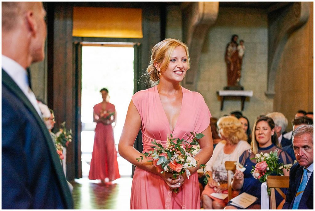 Bridesmaid walking down the isle in a pink dress during Italian destination wedding ceremony