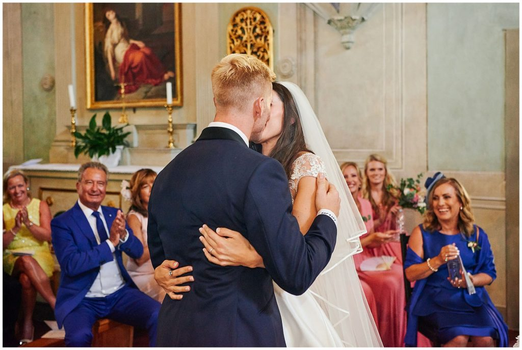 Bride and groom kissing during their wedding ceremony at the Catholic Church of Careggi
