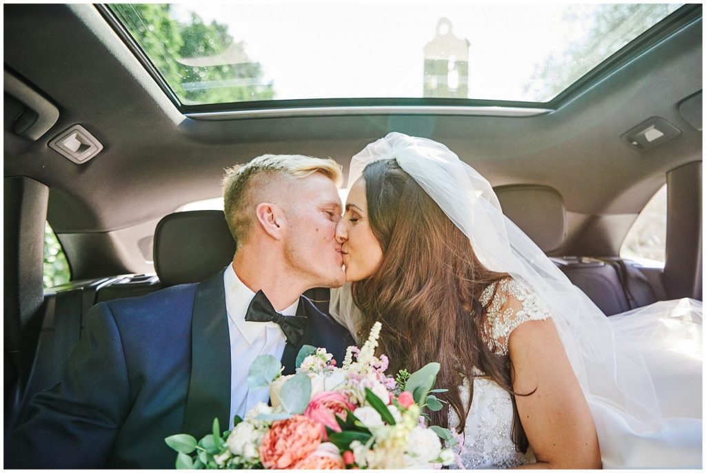 bride and groom kissing in wedding car in Florence, Italy