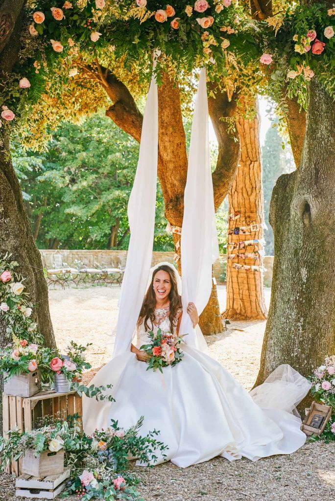 Bride sitting on white outdoor swing at villa le Fontanelle in Florence Italy