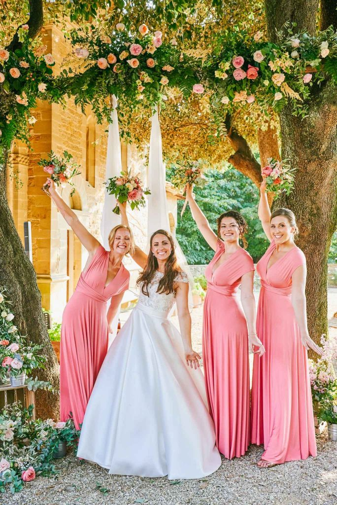 Bride with bridesmaids holding flowers in the air whilst outside at villa le Fontanelle in Florence Italy