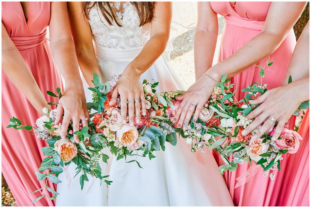Bride with bridesmaids hands on top of their wedding flowers showing 4 wedding rings.