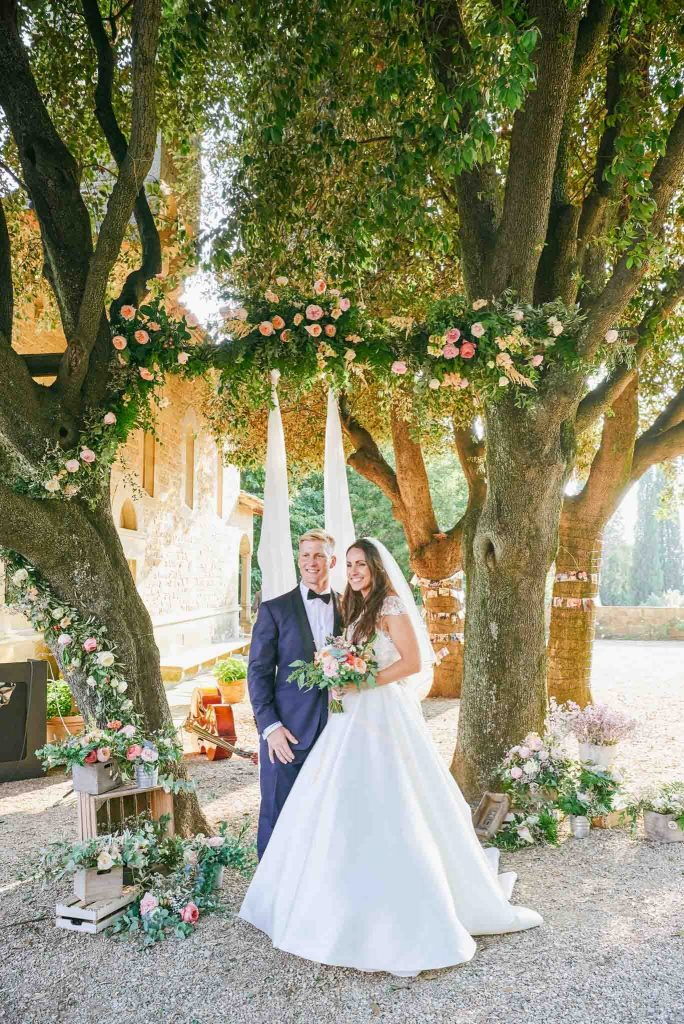 Bride and groom smiling in front of outside flower arch at the villa le Fontanelle in Florence Italy