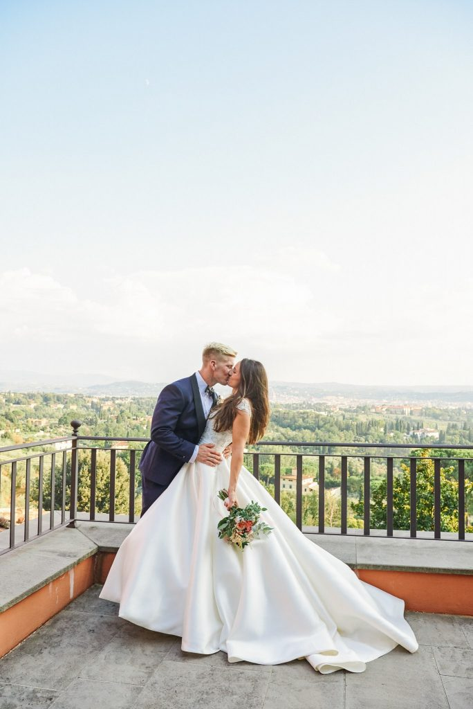 Bride and groom kissing in front of a stunning Tuscany view point