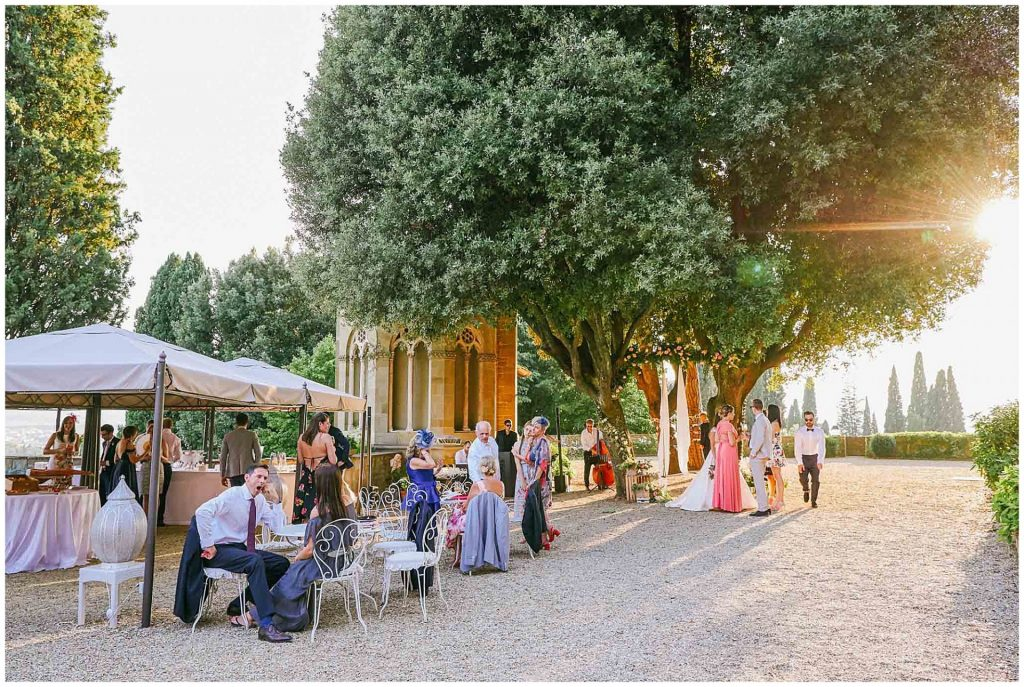 wedding guests relaxing and socialising on a beautiful summer day at villa le Fontanelle in Florence, Italy