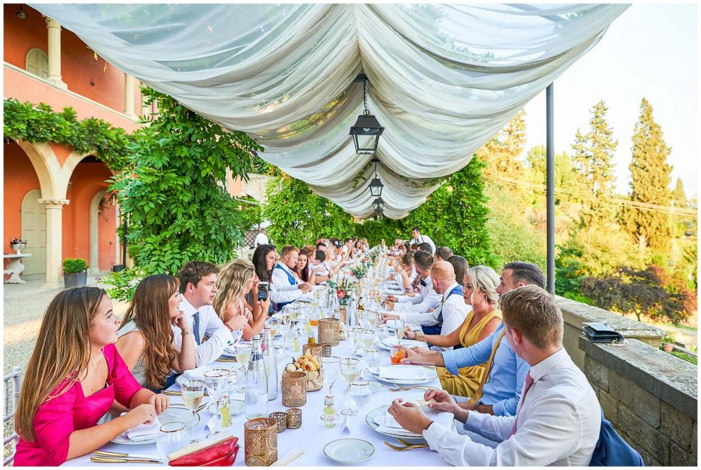 Wedding guests sat down at a long table overlooking a stunning view of Florence, Italy at villa le Fontanelle.