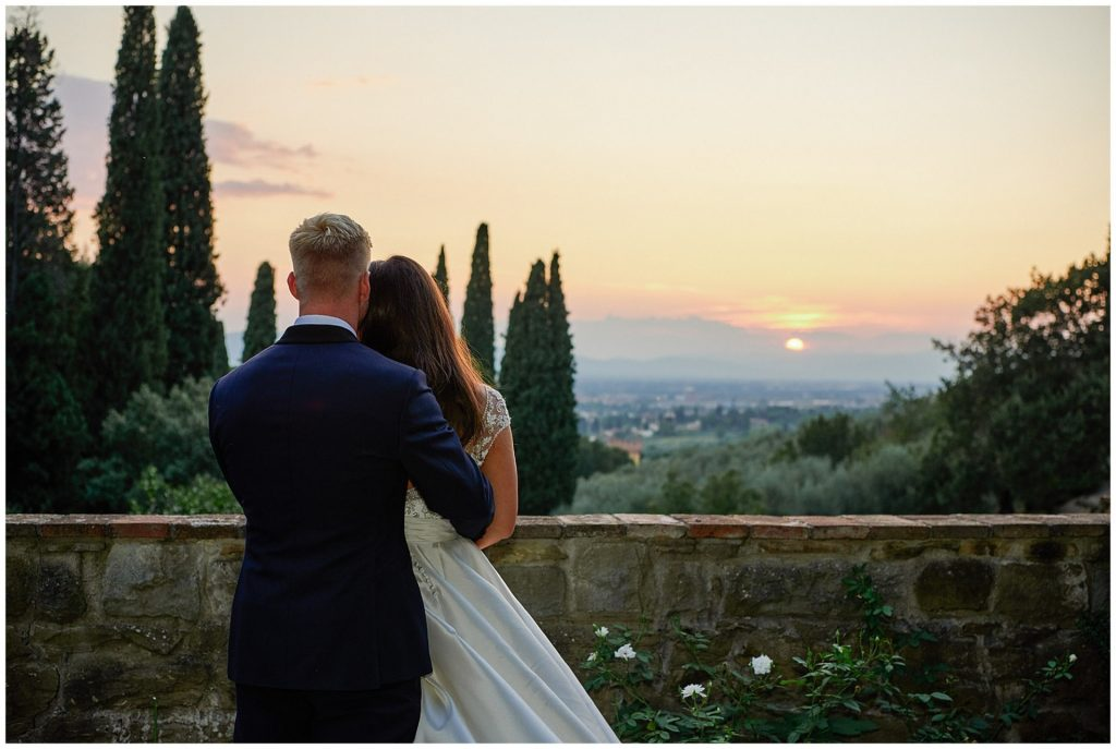 Bride and groom watching the tuscan sunset at the Villa le Fontanelle in Florence, Italy.