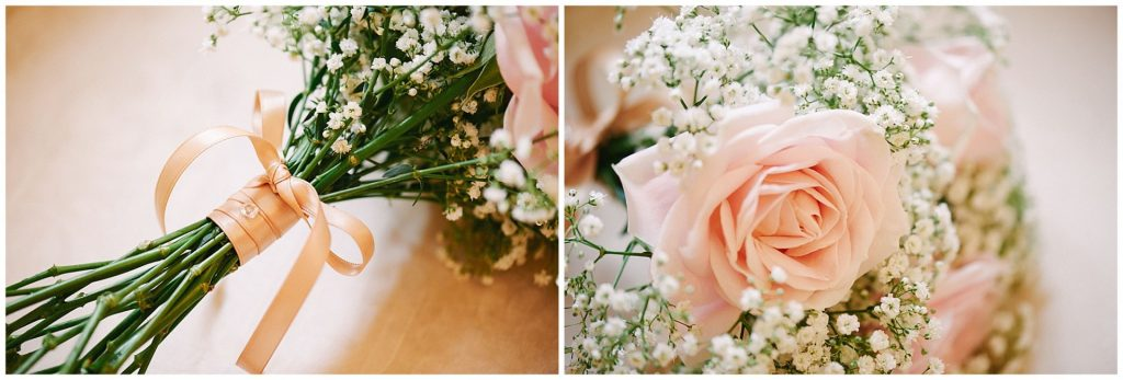 Wedding flower bouquet with pink roses and pink ribbon on a cream backdrop