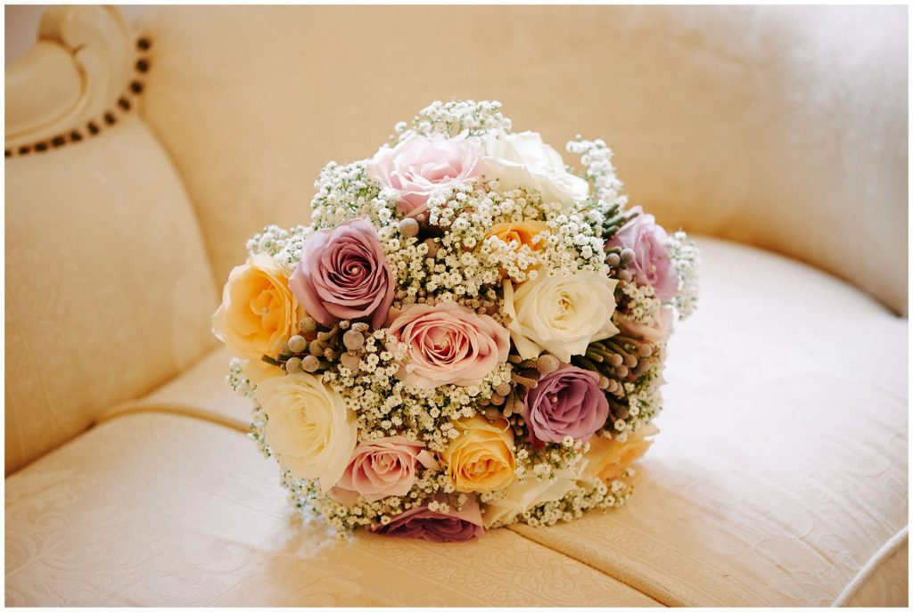 Wedding flower bouquet with white, pink and yellow roses sat on cream sofa.