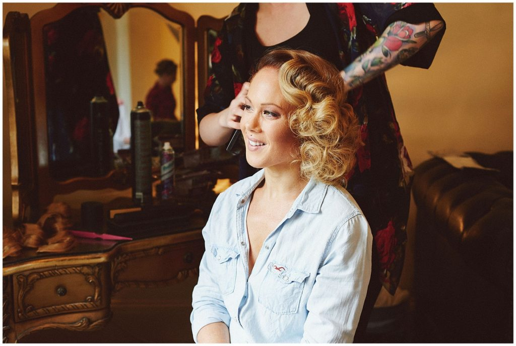 Bride smiling whilst having her hair styled into 1920's style waves.