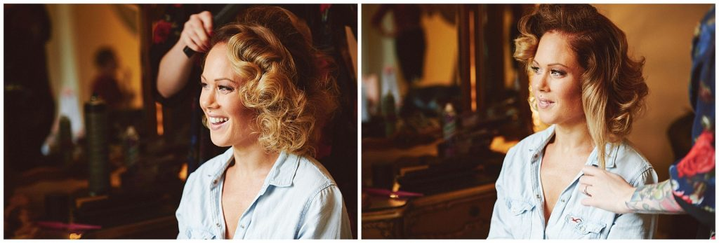 Bride smiling whilst having her hair styled in the dressing room at Woodhall Manor