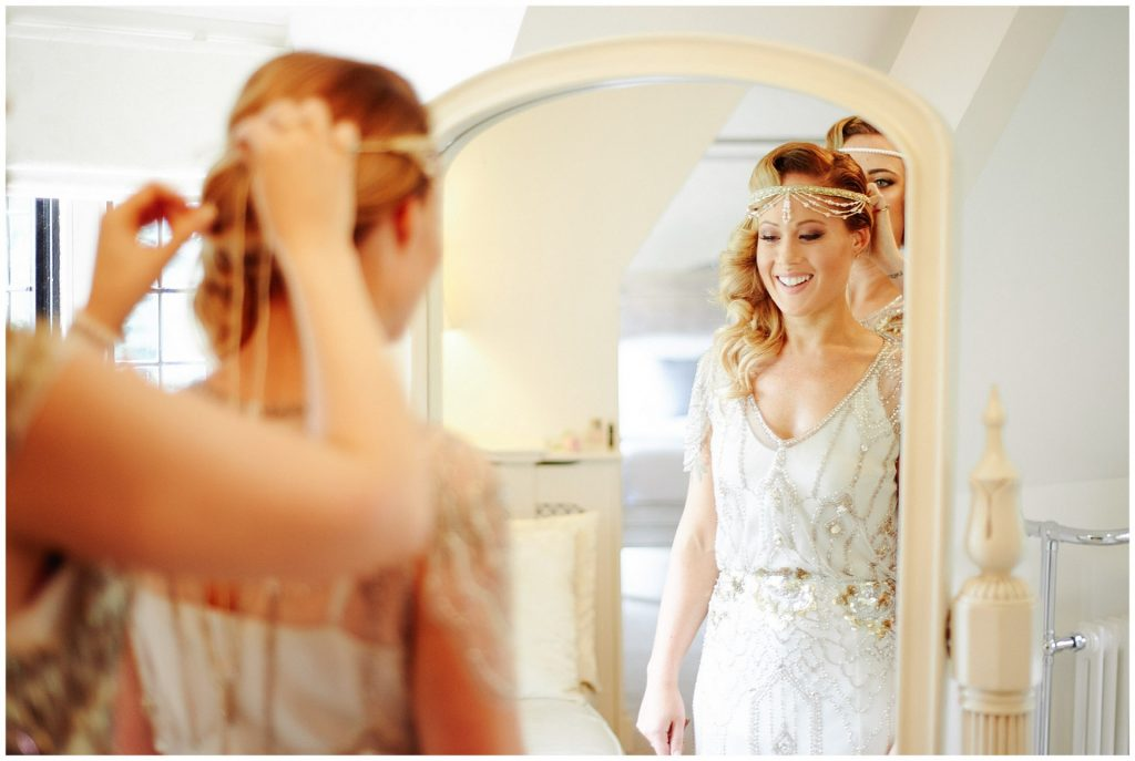 Bride smiling in mirror whilst bridesmaid helps her put on vintage 1920's jewellery head wear