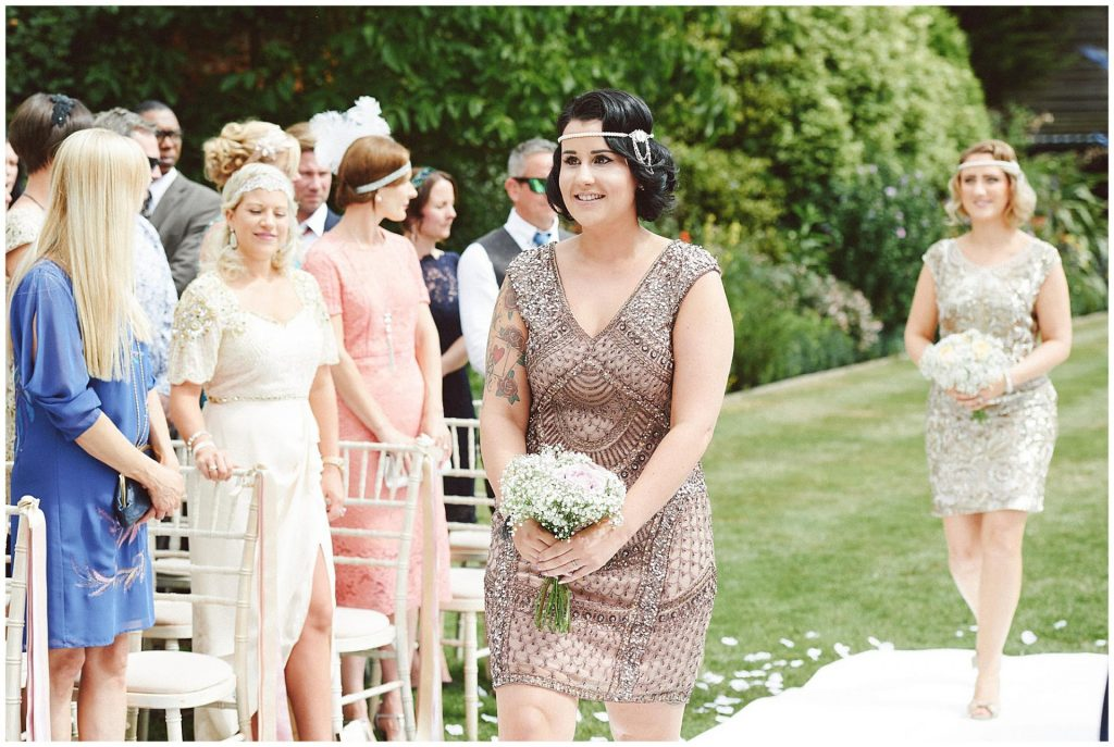 Vintage bridesmaid walking down outdoor wedding aisle, wearing a gold sequined dress and holding flowers