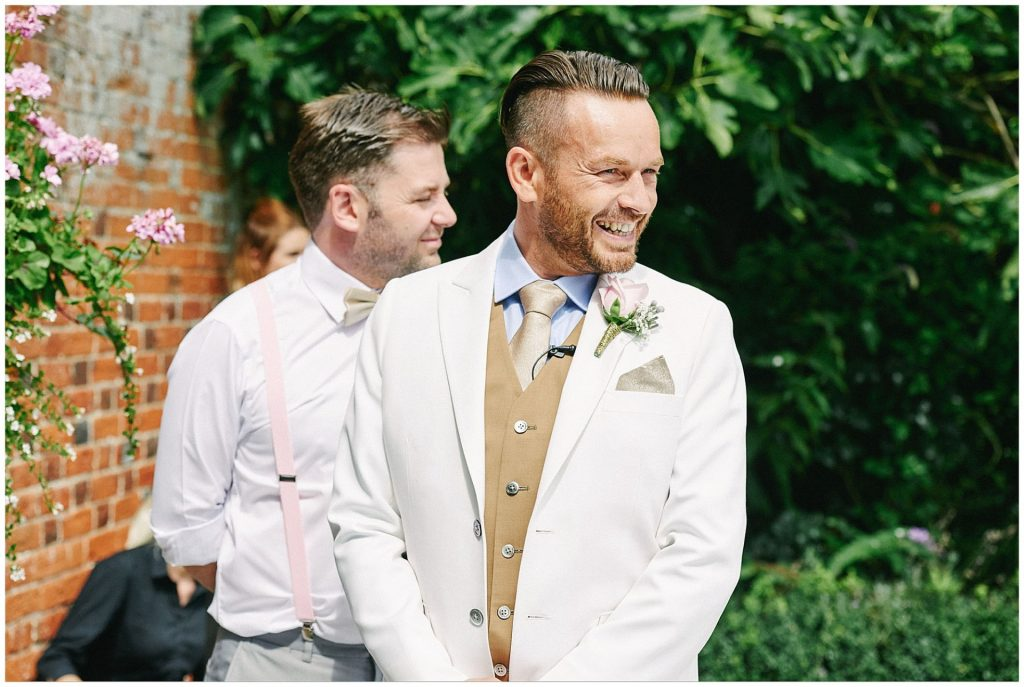 Groom wearing a white suit and laughing during his outdoor wedding ceremony at Woodhall Manor