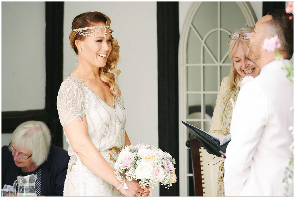 Vintage looking bride laughing whilst holding flowers during outdoor ceremony at Woodhall Manor