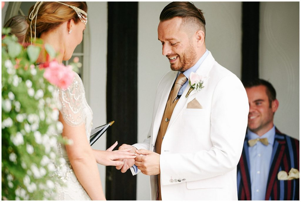 Dapper looking groom laughing whilst exchanging rings during his outdoor wedding ceremony at Woodhall Manor