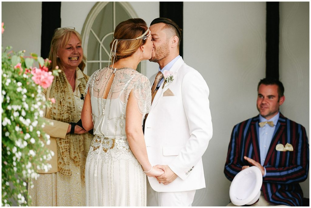 19020's style vintage bride and groom sharing their first kiss during  outdoor wedding ceremony at Woodhall Manor