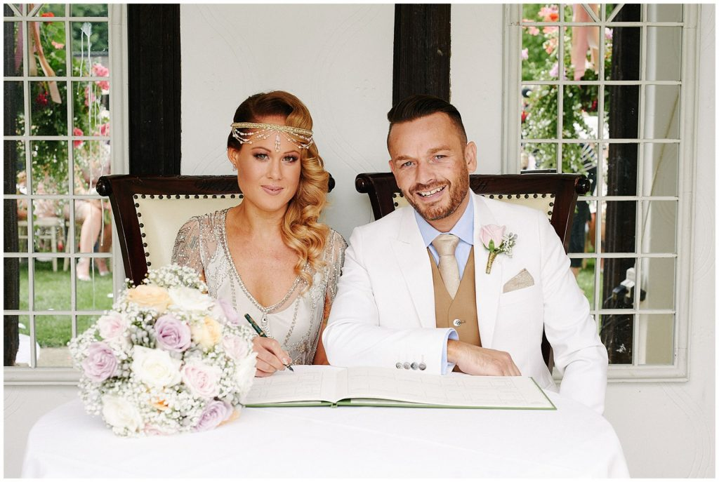 vintage bride and groom signing the register during their outdoor wedding ceremony at Woodhall Manor in Suffolk, UK.