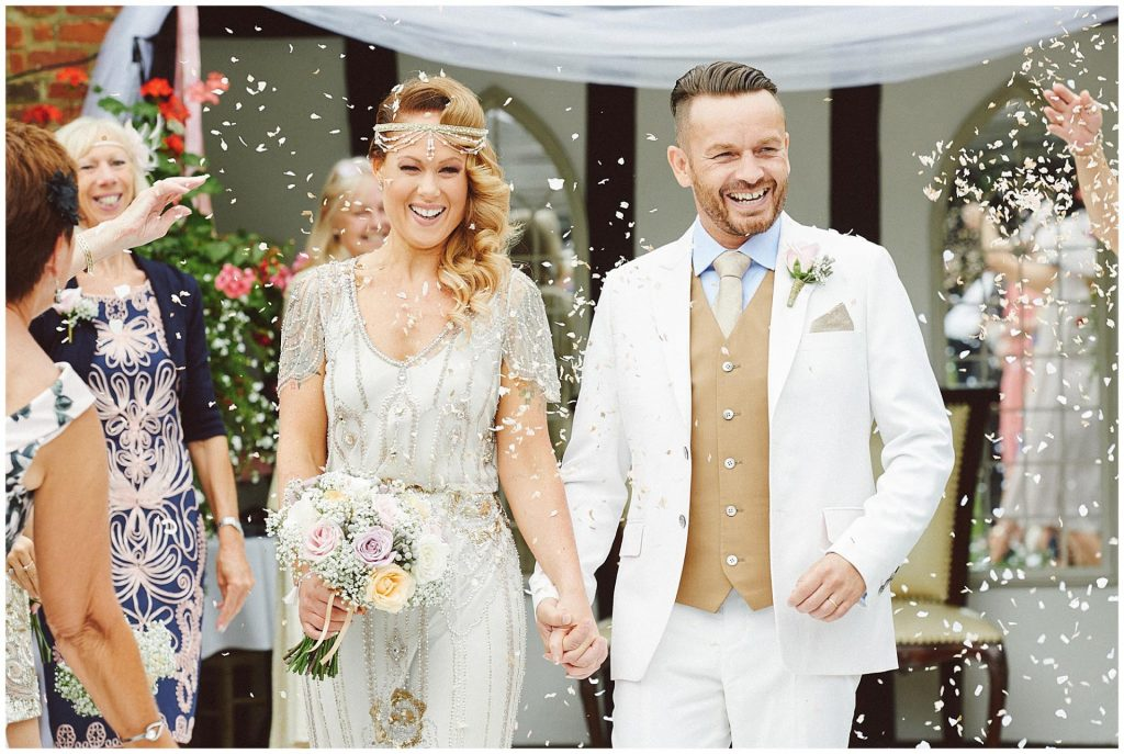 Happy bride and groom walking back down outdoor aisle whilst confetti is thrown over them at Woodhall Manor in Suffolk, UK.