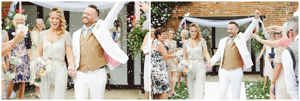 Bride and groom celebrating whilst confetti is thrown over them during outdoor wedding ceremony at Woodhall Manor in Suffolk
