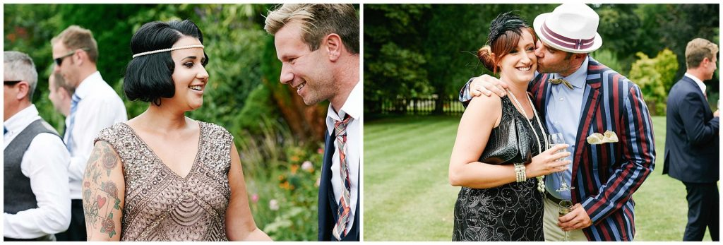 1920's themed wedding guests socialising and laughing in the gardens at Woodhall Manor in Suffolk