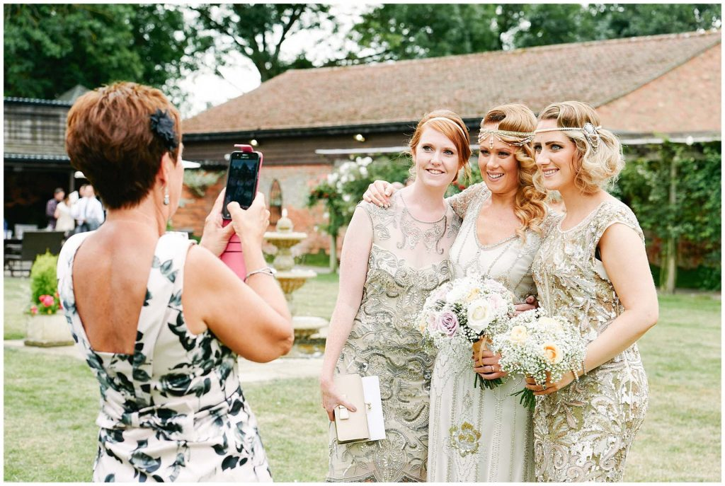 Bride having her photo taken with vintage looking wedding guests in the gardens at Woodhall Manor