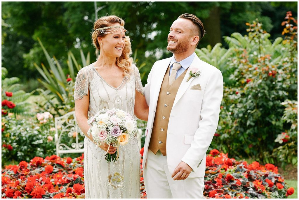 1920's themed bride and groom laughing in front of colourful flowers at Woodhall Manor in Suffolk