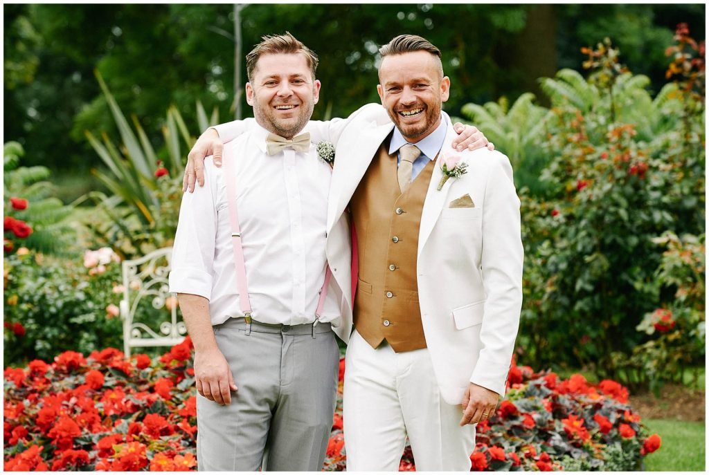 Groom wearing white suit laughing with his best man in front of colourful flowers at Woodhall Manor