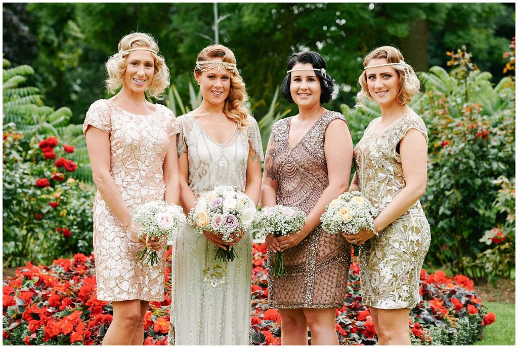 Bride with her 1920's flapper style bridesmaids holding flower bouquets in the gardens at Woodhall Manor in Suffolk