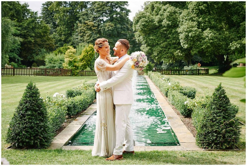 Vintage bride and groom on a sunny day in front of the water feature at Woodhall Manor