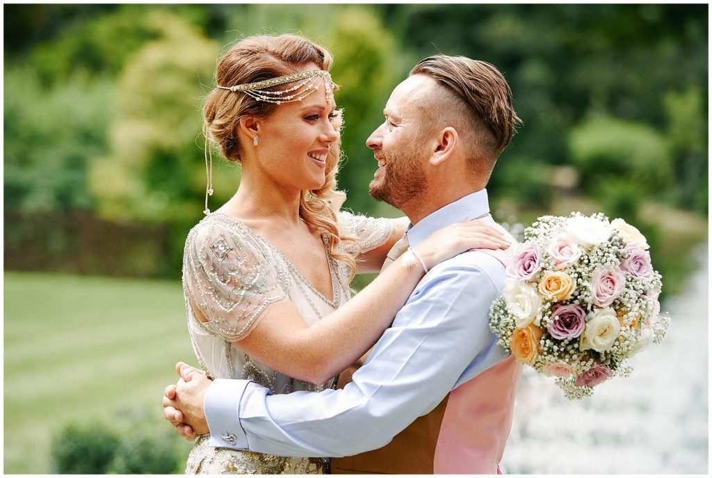 Vintage bride with her arms around her groom whilst holding flowers on a sunny day at Woodhall Manor, suffolk