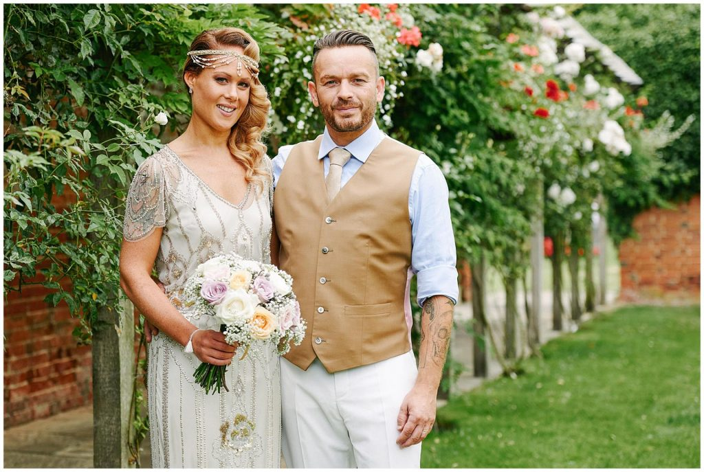 Vintage styled Bride and Groom smiling together whilst stood in the gardens at Woodhall Manor in Suffolk