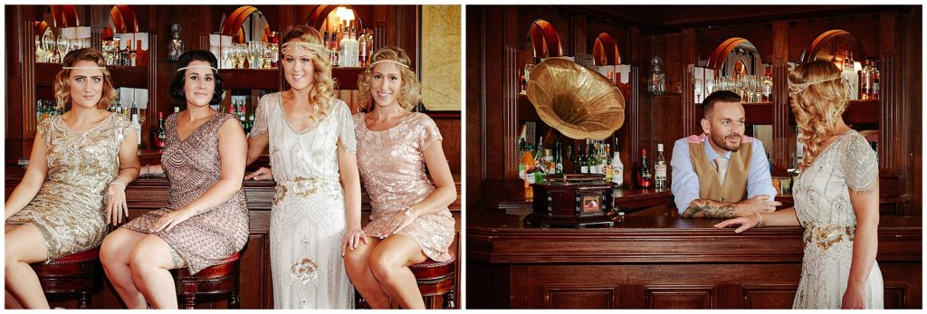 1920's Great Gatsby themed Bridal party posed and smiling by the bar at Woodhall Manor in Suffolk