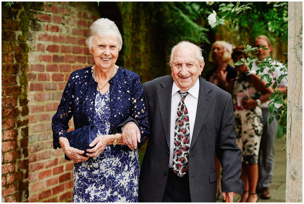 Grandparents smiling whilst walking through the gardens at Woodhall Manor in Suffolk