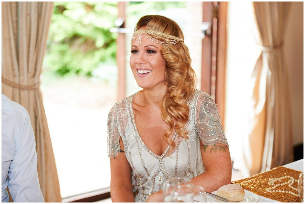 1920's style bride laughing during speeches at Great Gatsby themed wedding