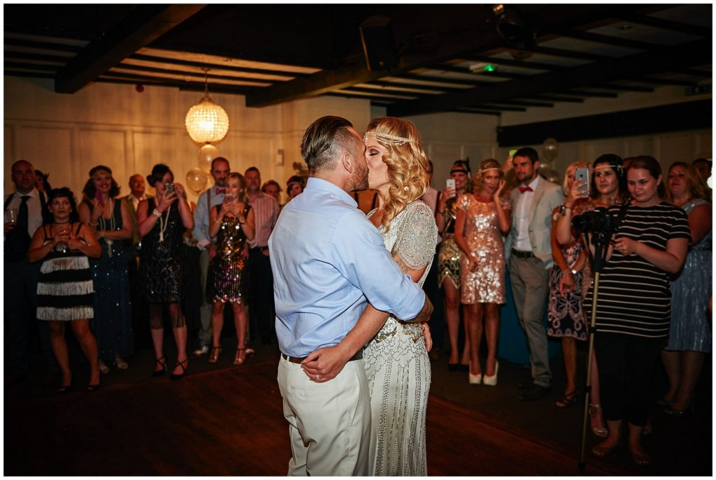 1920's style bride and groom kissing during their first dance at Woodhall Manor in Suffolk