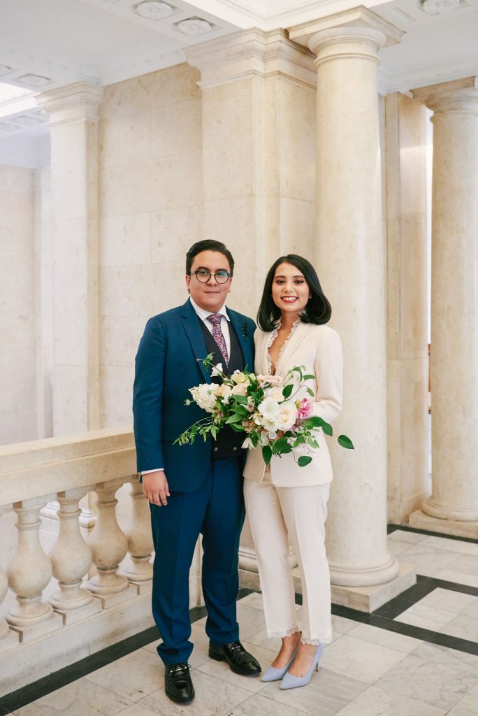 bride wearing white pantsuit with groom n blue suit at Old Marylebone Town Hall in Central London.