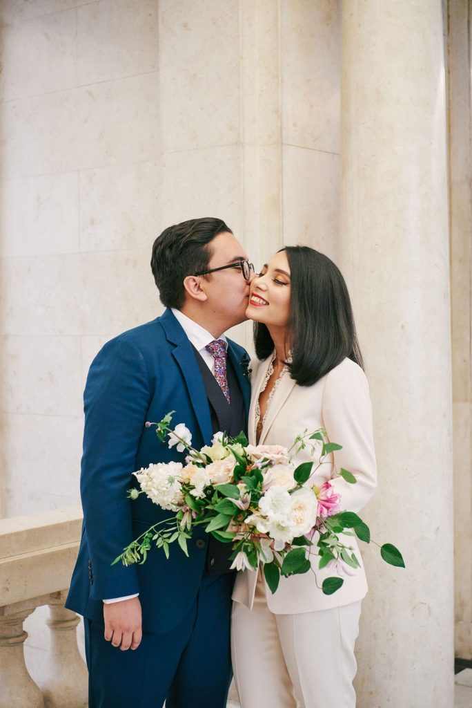 Bride and groom kissing in front of white marble at Old Marylebone Town Hall in Central London.