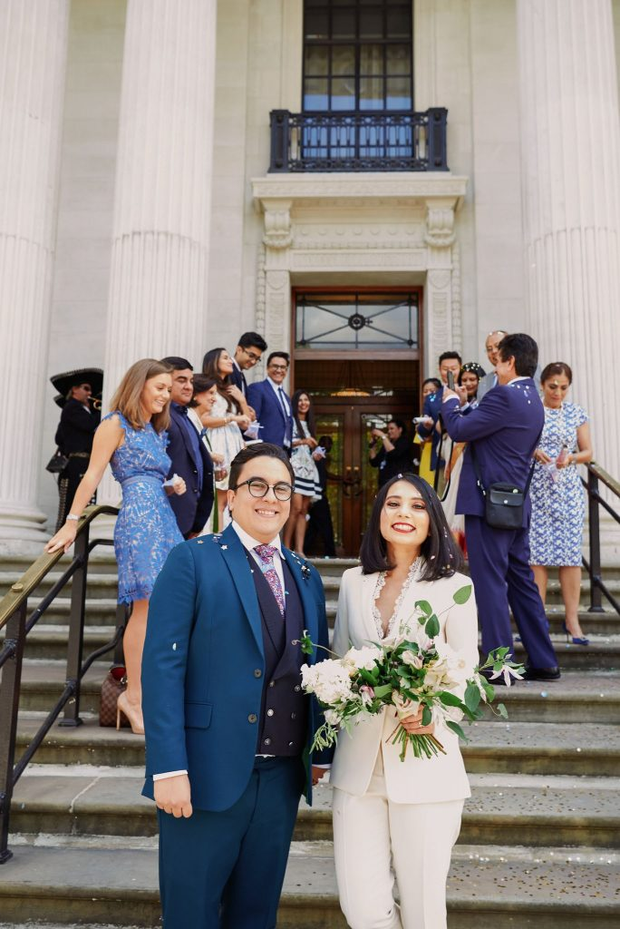 Bride and groom smiling at the bottom of the steps after exiting The Old Marylebone Town Hall in Central London