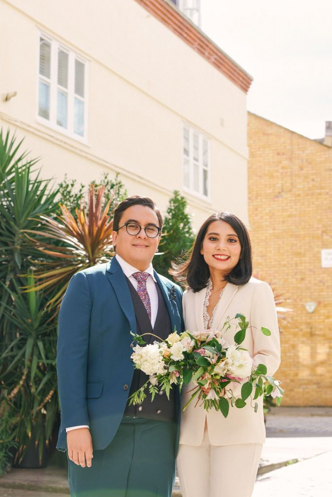 Bride and groom smiling together on a brick street with green plants in Marylebone, London.