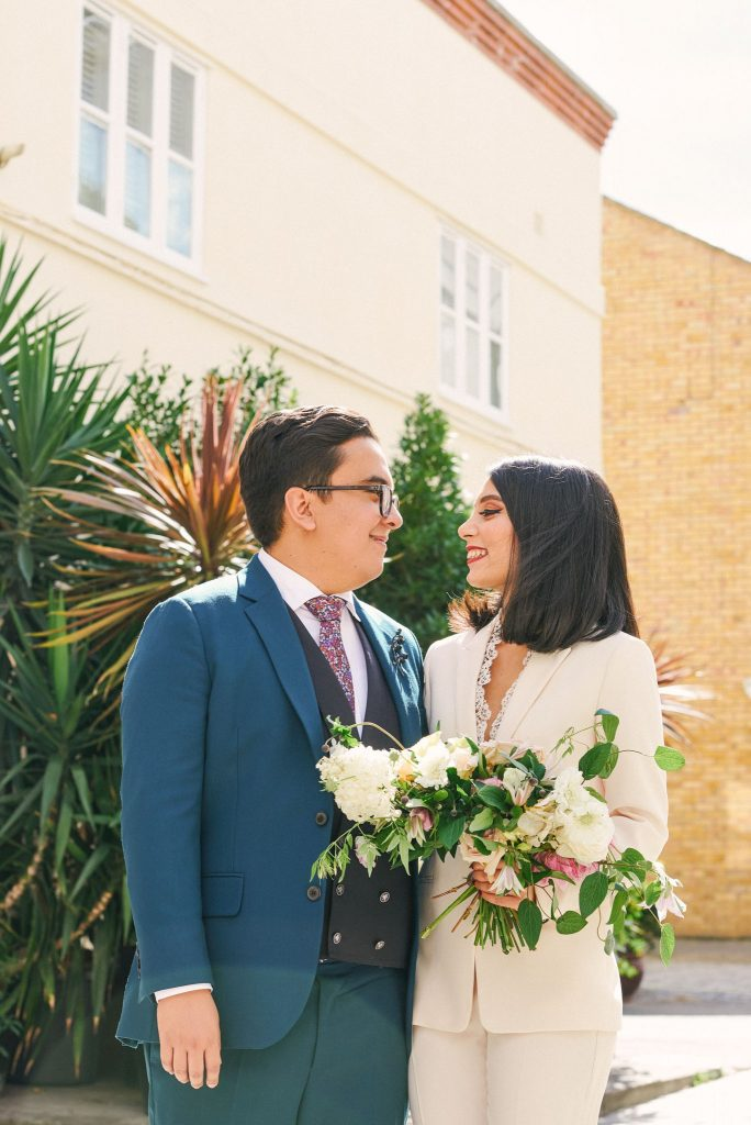 Bride and groom smiling together on a sunny day on a brick street in Marylebone, London.