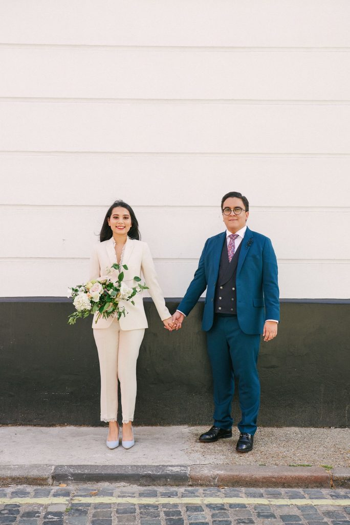 Bride and groom holding hands in front of black and white wall in central London.
