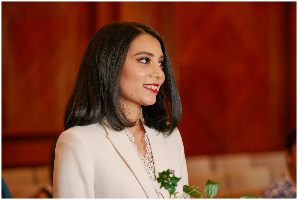 Bride smiling during wedding ceremony in the Westminster Room at Marylebone Town Hall