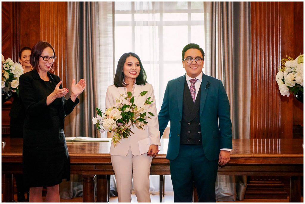 Bride and groom holding hands and smiling in the westminster room at Old Marylebone Town Hall