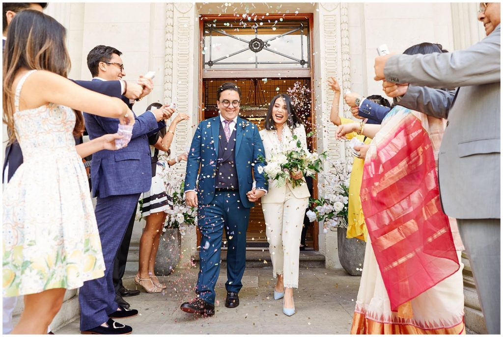 Bride and groom exiting The Old Marylebone Town Hall in Central London whilst wedding guests throw confetti at them