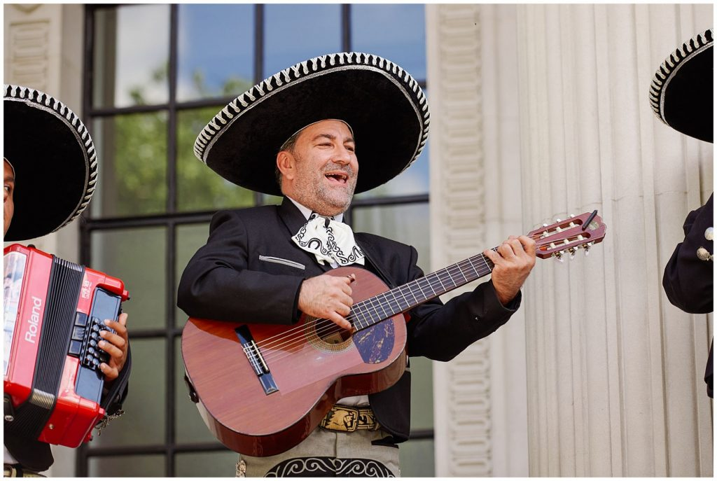 Mexican mariachi man playing his gutiar outside of The Old Marylebone Town Hall on wedding day