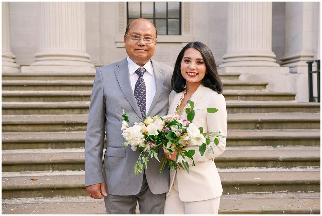 Bride with her dad at the bottom of the steps outside The Old Marylebone Town Hall