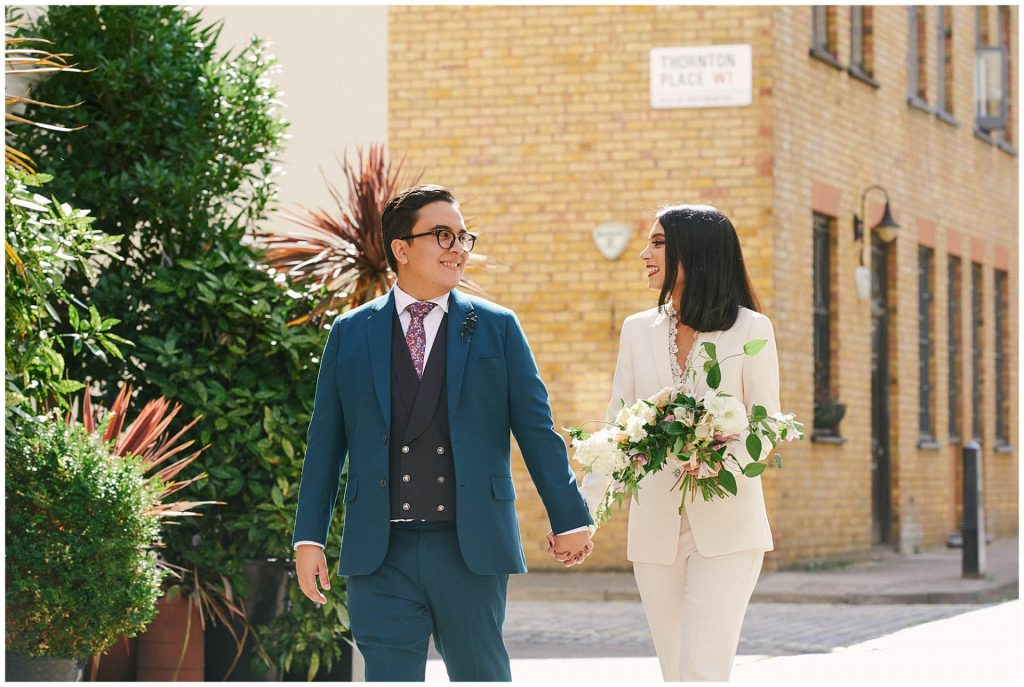 Bride and groom holding hands and walking through brick streets with green plants in Marylebone, London.